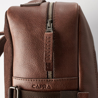 YKK metallic zippers detail. Custom monogrammed brown leather backpack for men