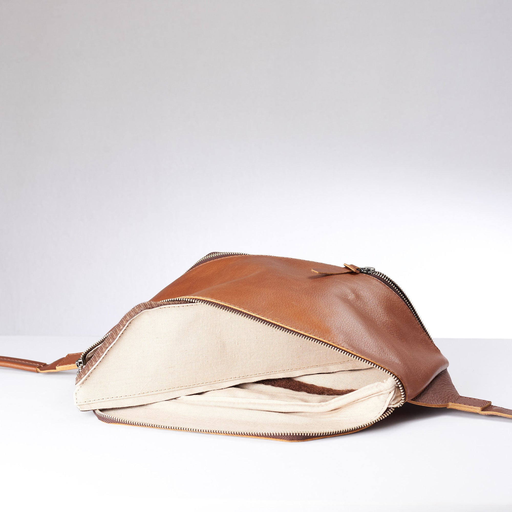 Tan Fenek sling bag backpack made by Capra Leather. Frontal view of small leather crossbody and single strap.