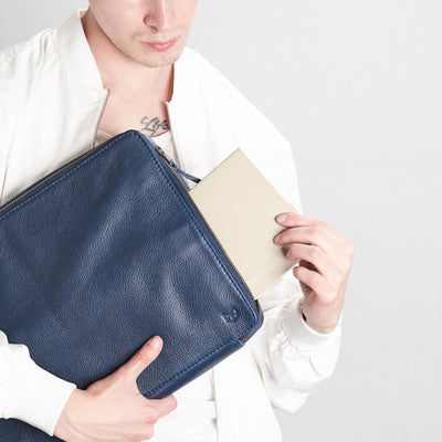 Model using tech bag .handmade blue leather tech laptop tablet bag is perfect to travel organized.