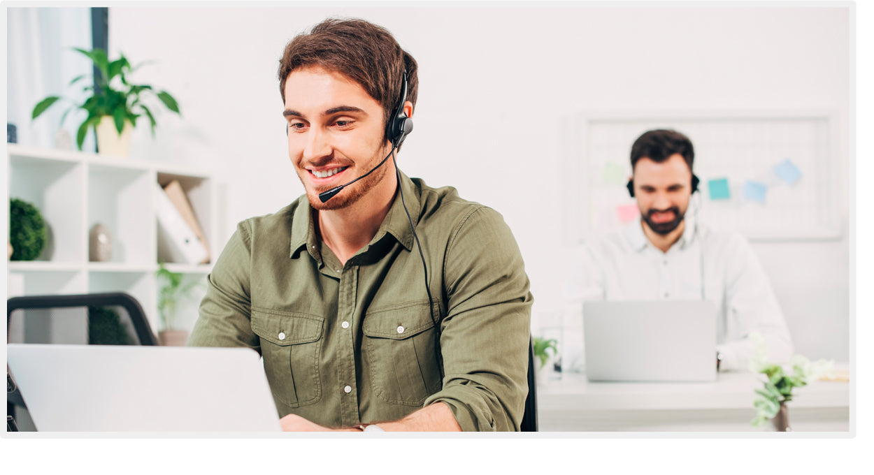 Man working in IT support wearing a headset at work