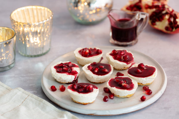 Seven Red Christmas Cheesecake Minis on white plate with Scattered Pomegranate Seeds