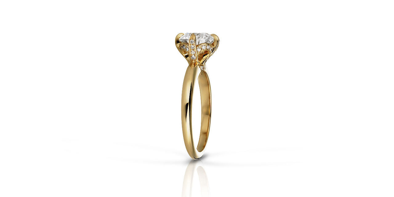 A photograph of the side of a yellow gold solitaire engagement ring with diamond set prongs
