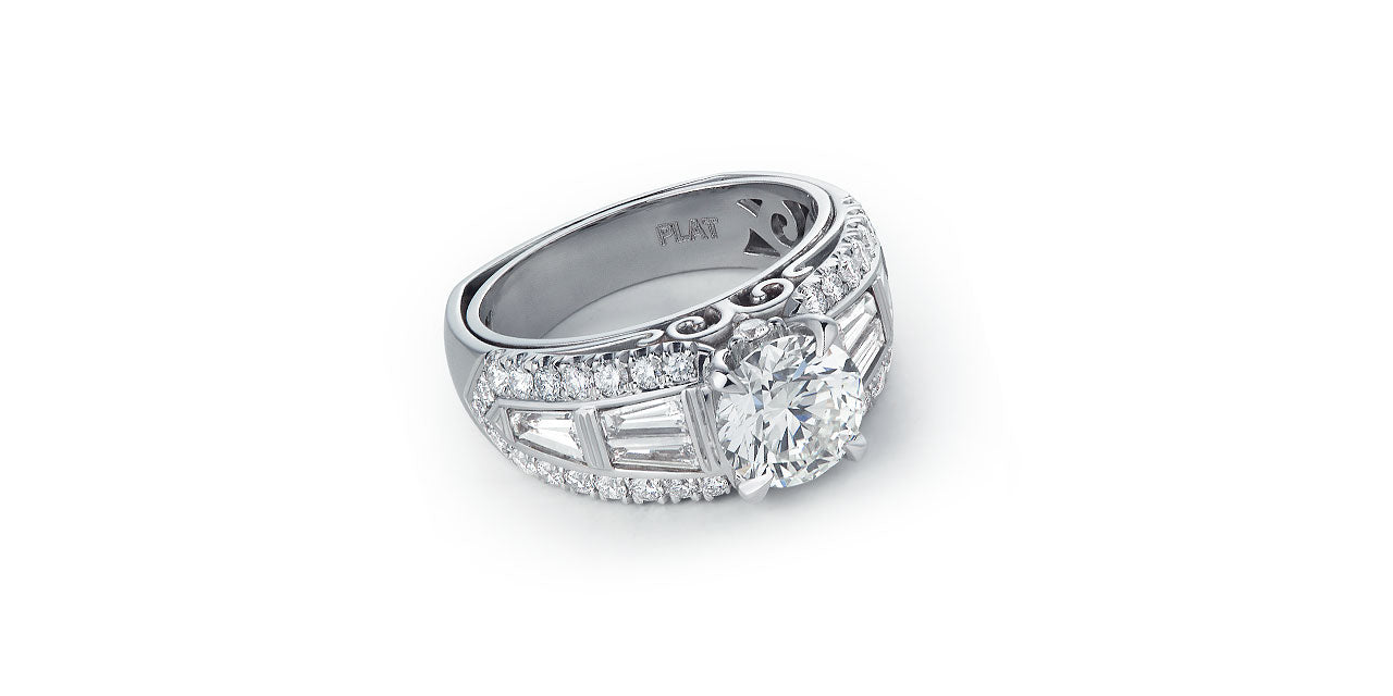 A platinum and diamond wide wedding ring with a round center diamond and a baguette diamond band bordered by round diamonds. A script initial M is in the undergallery.