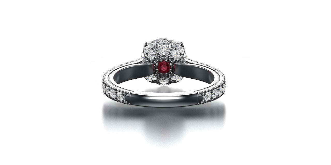 An underneath view of a platinum and diamond engagement ring with a lotus flower head and hidden garnet birthstone.