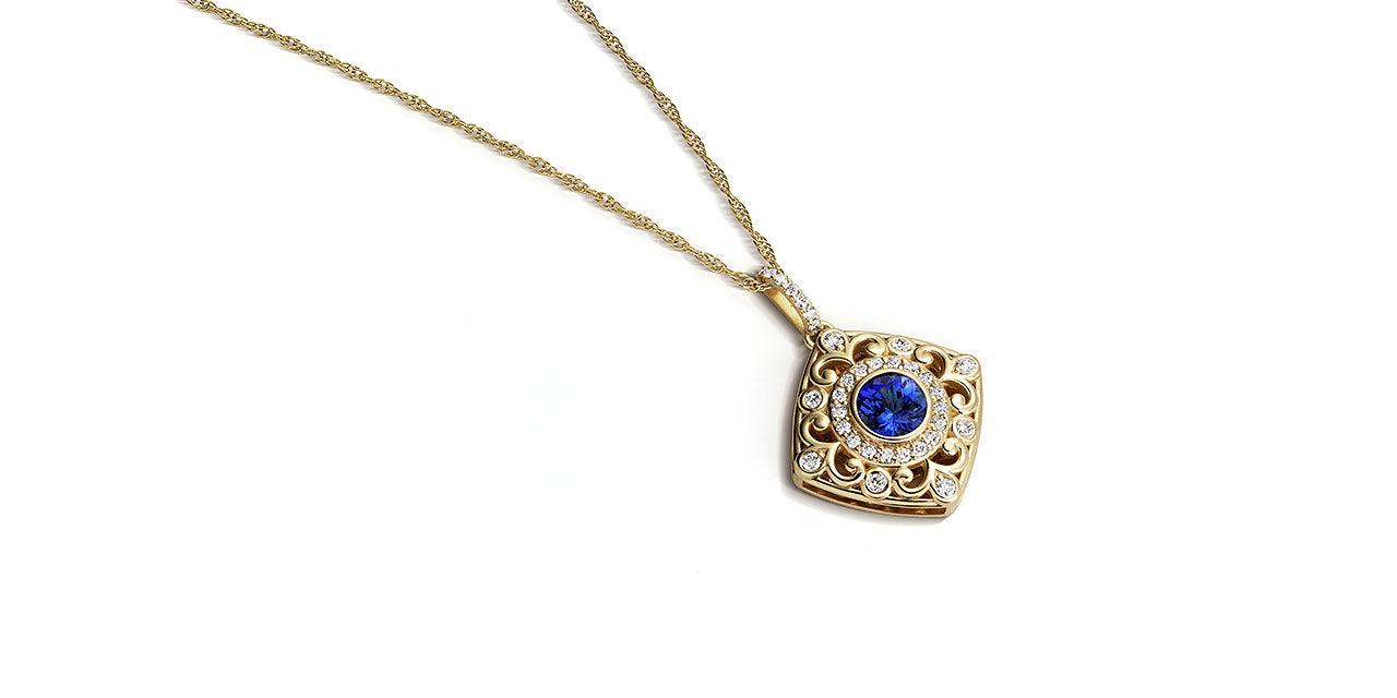 A photograph of a yellow gold Tanzanite pendant with a soft square shape and filigree and diamond details laying down.