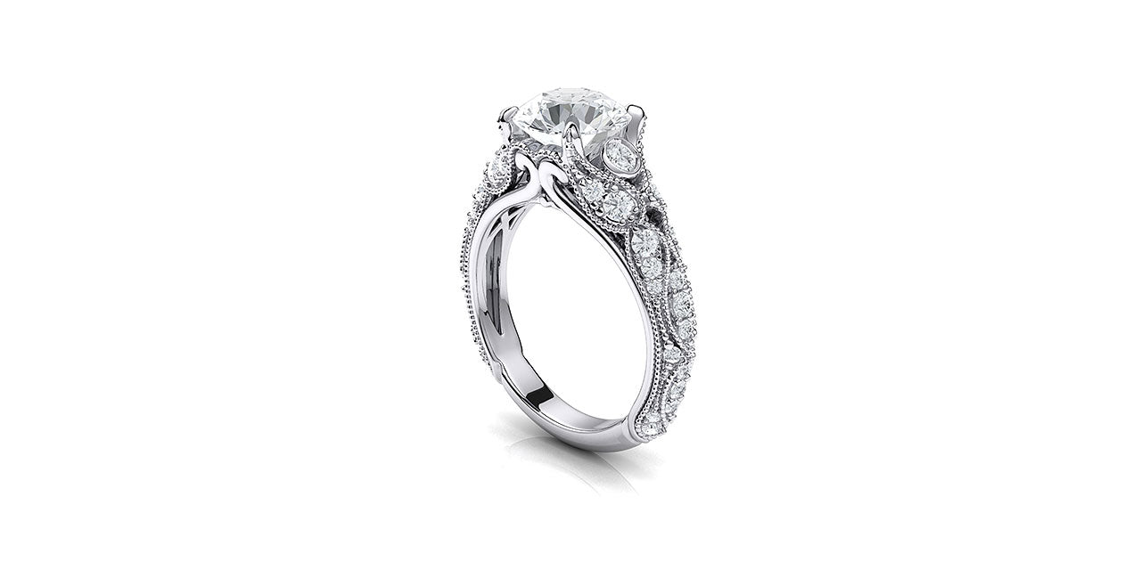 A perspective view of a vintage style diamond engagement ring with leaf and petal inspired shapes forming the sides of the ring.