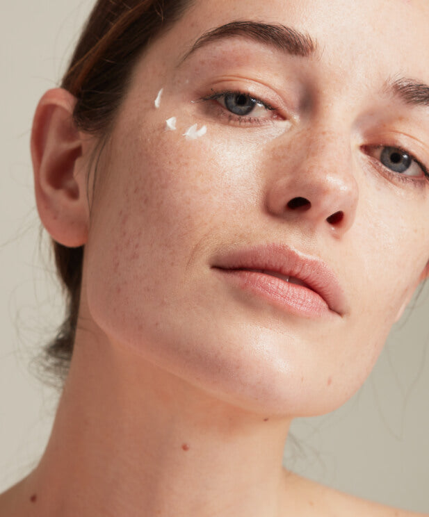 woman with eye cream on face