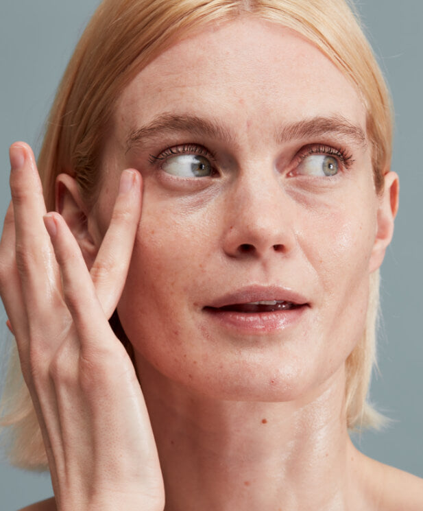 woman with bare skin touching her face