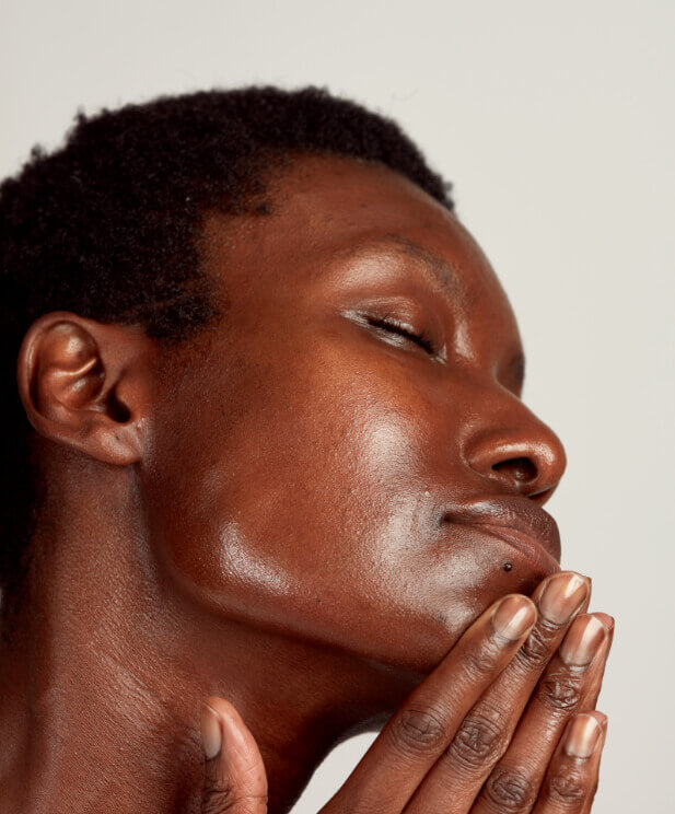 black woman touching cleansed face