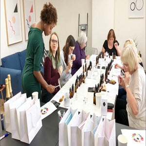 Group of glamorous women making bespoke perfumes in perfume making workshop in Hatton Garden with prosecco and cupcakes
