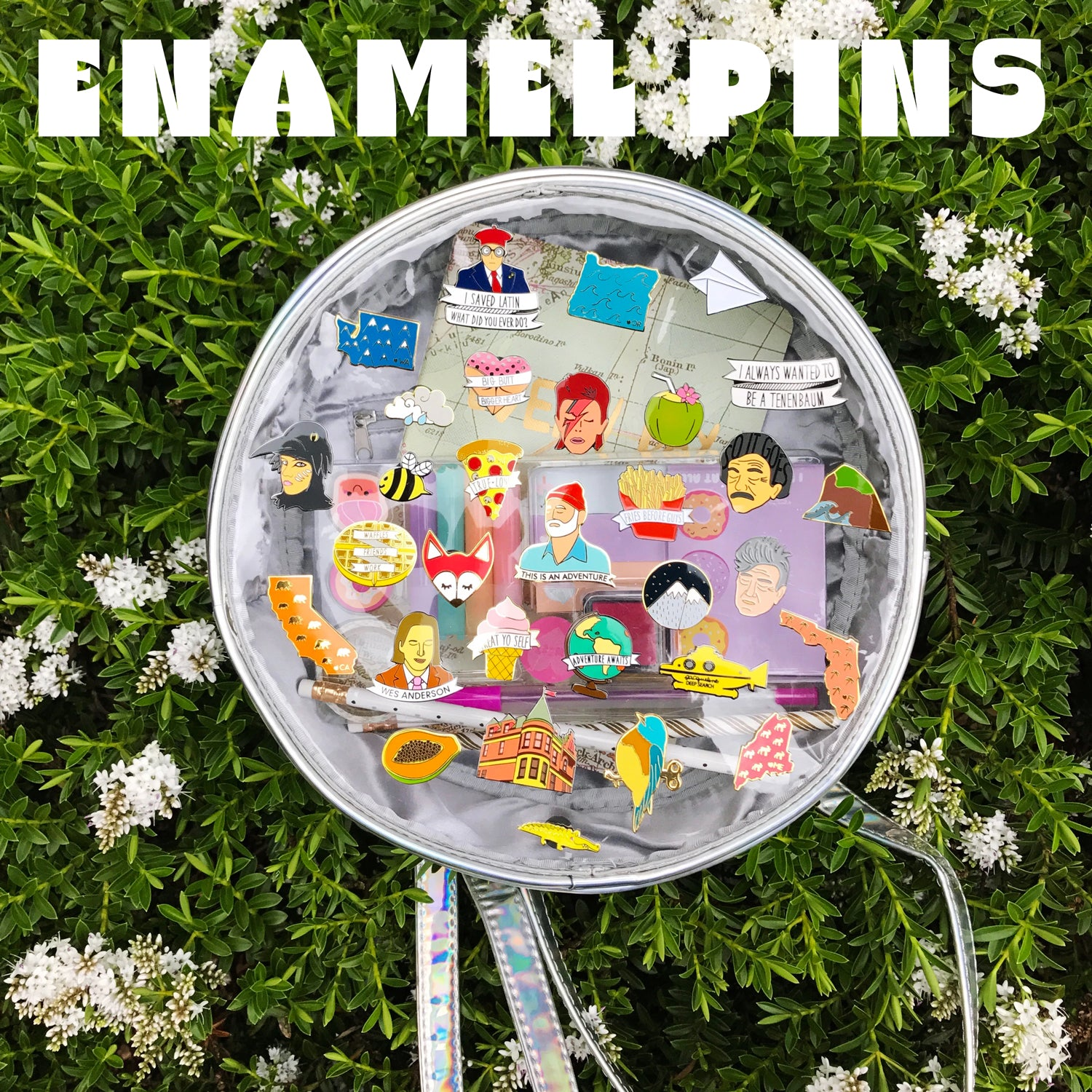 Various enamel pins on a holographic circle purse with clear window on a flowery bush