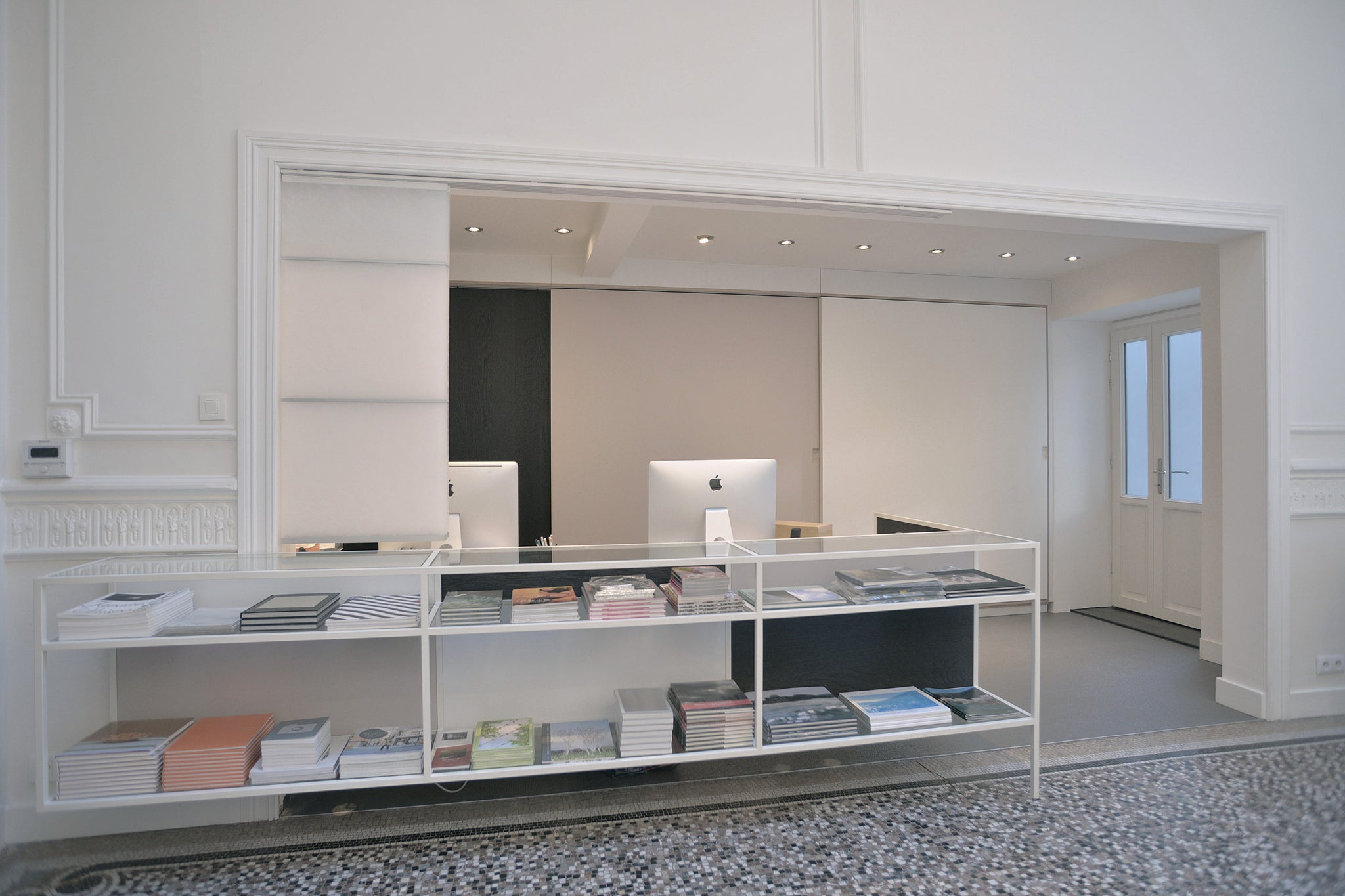 Office desk with book display rack and built-in kitchen at Ibasho Gallery, Antwerp