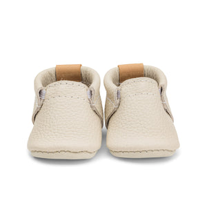 Photo of a cream coloured leather baby shoe from Heyfolks, against a white background.