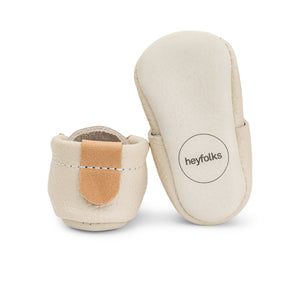 Photo of a cream coloured leather baby shoe from Heyfolks, with one shoe in an upright position and against a white background.