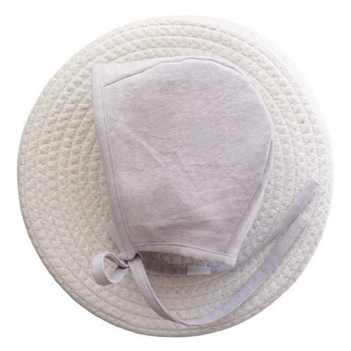 Photo of baby bonnet in a light grey linen fabric.