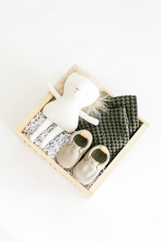 Top view of LEO gift box featuring lion stuffy, leather baby shoes, and a pair of olive waffle washcloths in a signature wooden box.
