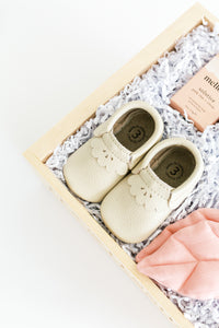 Close up photo of ROSE gift box from a top view, focusing in our leather baby shoes in a cream with scalloped edge.