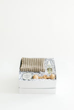 Load image into Gallery viewer, Front view photo of SERENE box featuring a pair of waffle washcloths, organic baby balm, foaming baby wash, and wooden rattle toy.