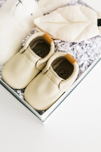 Close up photo of cream leather baby shoes from theARCTIC gift box