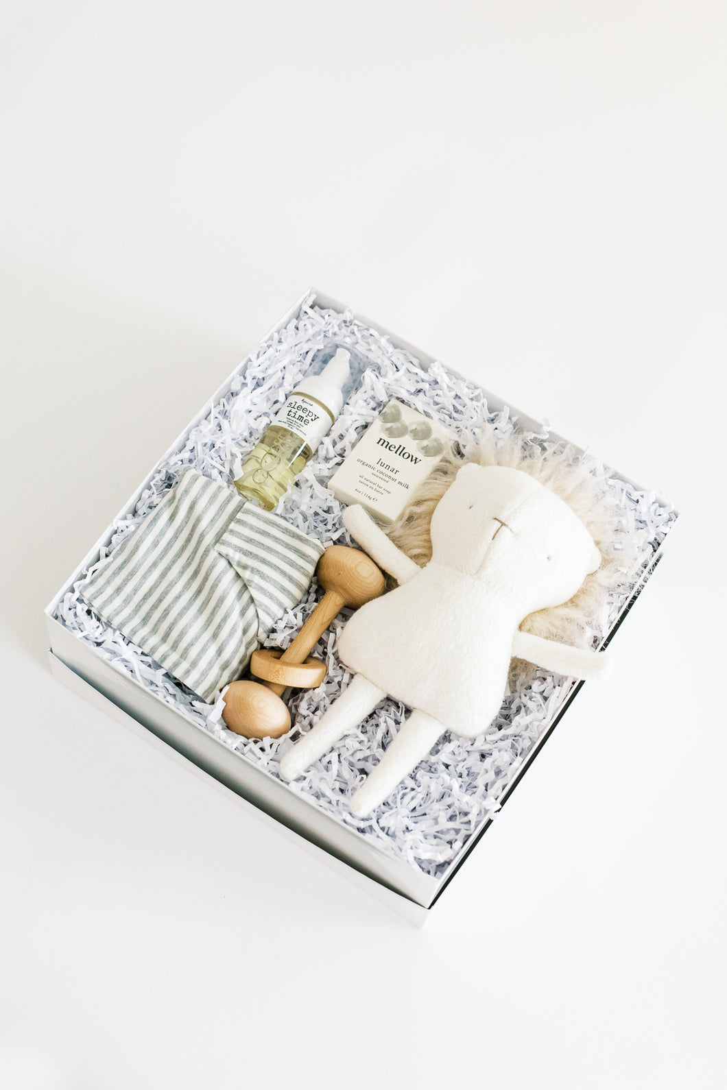 Top view photo of Bebé gift box on a white background, including foam wash, unscented soap, wooden rattle toy, grey and ivory striped romper, and stuffed lion toy.