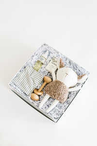 Top view photo of Bebé gift box on a white background, including foam wash, unscented soap, wooden rattle toy, grey and ivory striped romper, and stuffed sheep toy.