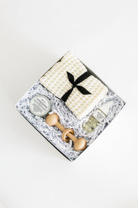 Photo of SERENE baby gift box with vanilla waffle washcloths, organic baby balm, wooden rattle, and baby foaming wash. Pictured on a white background.
