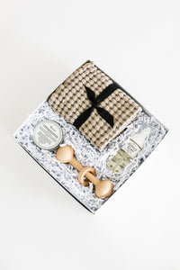 Photo of SERENE baby gift box with taupe waffle washcloths, organic baby balm, wooden rattle, and baby foaming wash. Pictured on a white background.