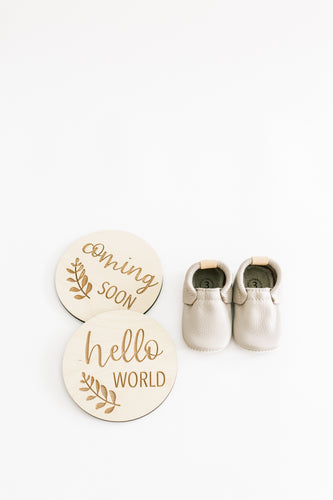Photo of leather baby shoes and two wooden announcement rounds with HELLO WORLD and COMING soon laser-engraved, on a white background.