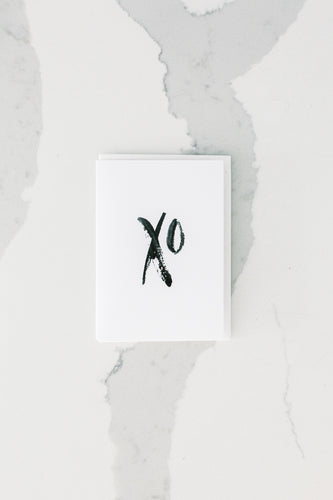 Photo of white greeting card with XO in black hand-painted design.