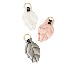 Load image into Gallery viewer, Photo of three organic baby leaf-shaped teethers in grey, dusty rose, and ivory organic gauze with a raw beechwood ring.