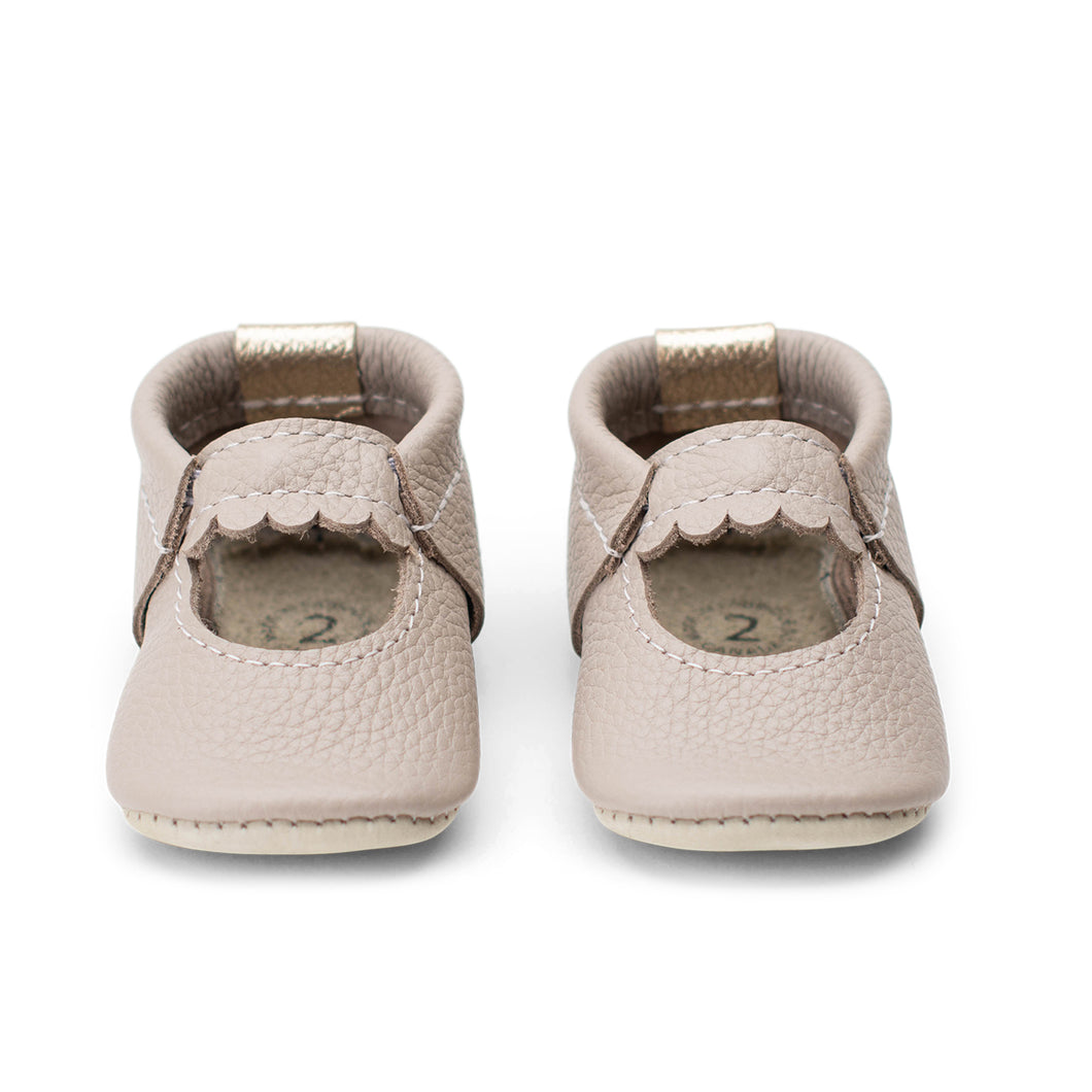 Photo of a pair of baby shoes in a muted light brown with a slight mauve undertone leather in a mini-jane style.