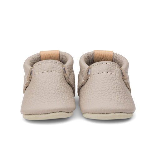 Photo of leather baby shoes in a muted brown with mauve undertones.