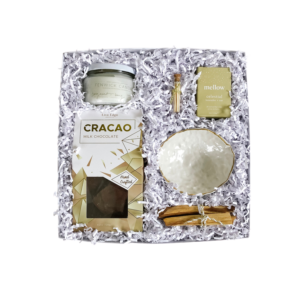 The TINSEL box from Lex & Lennon Gift's holiday collection. Featuring a bergamot + bay coconut wax candle accompanied by white tipped matches, milk chocolate cracao, porcelain ring bowl with 24K gold rim, bundle of palo santo, and bar of lavender + oat soap.