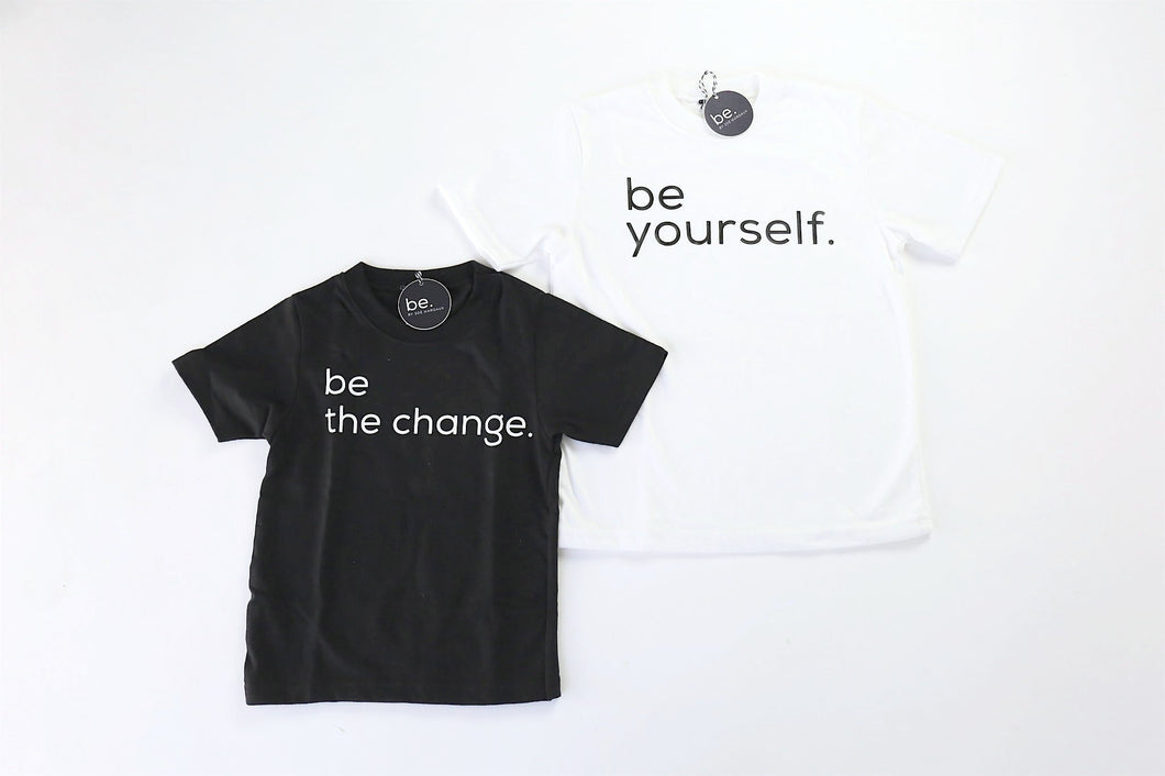 Photo of two monochrome t-shirts for kids. First t-shirt is black with BE THE CHANGE in a white font. The second t-shirt is white with BE YOURSELF in black font.