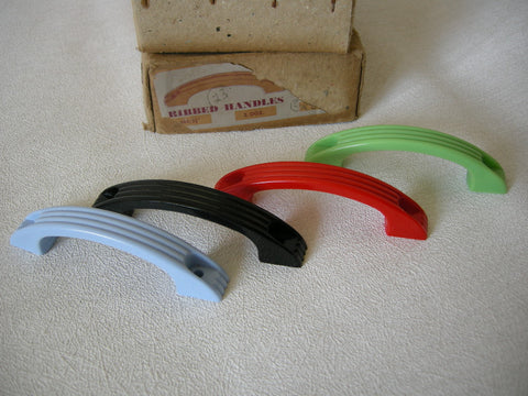 Colourful unused small plastic pull handles from the 1950s in blue, red, green and black