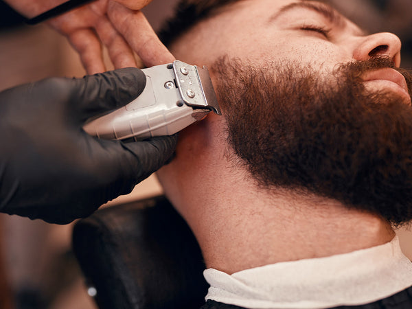 barber using clippers on a customer's beard