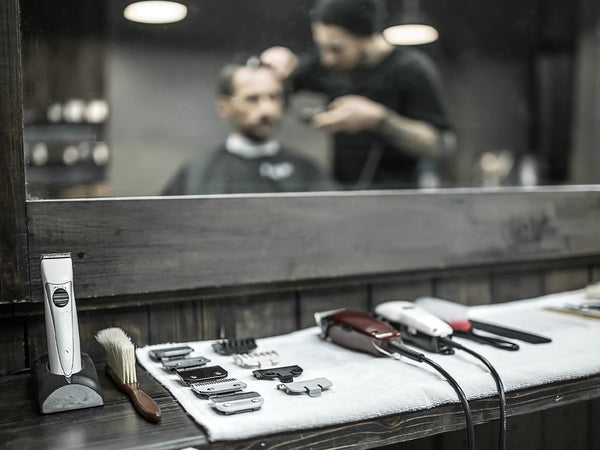 hair trimmers on counter in front of mirror with barber and customer reflected in mirror