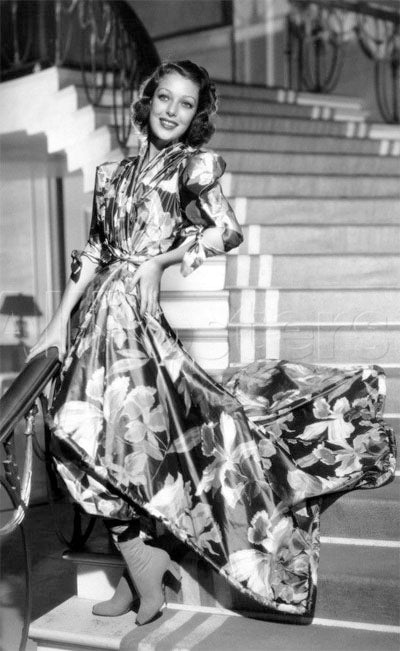 Loretta Young waiting for guests to arrive in her floral hostess gown and ankle boots in 1937