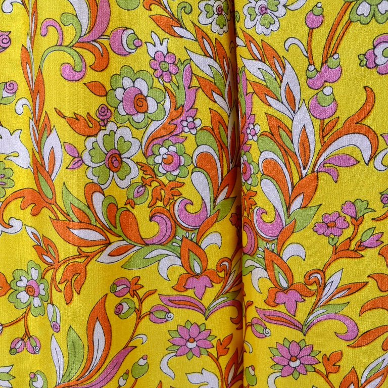 Detail of silk jumpsuit green, orange, pink, yellow floral pattern