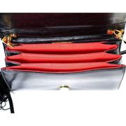 Red inside of the patent leather black Judith Leiber handbag with brass animals