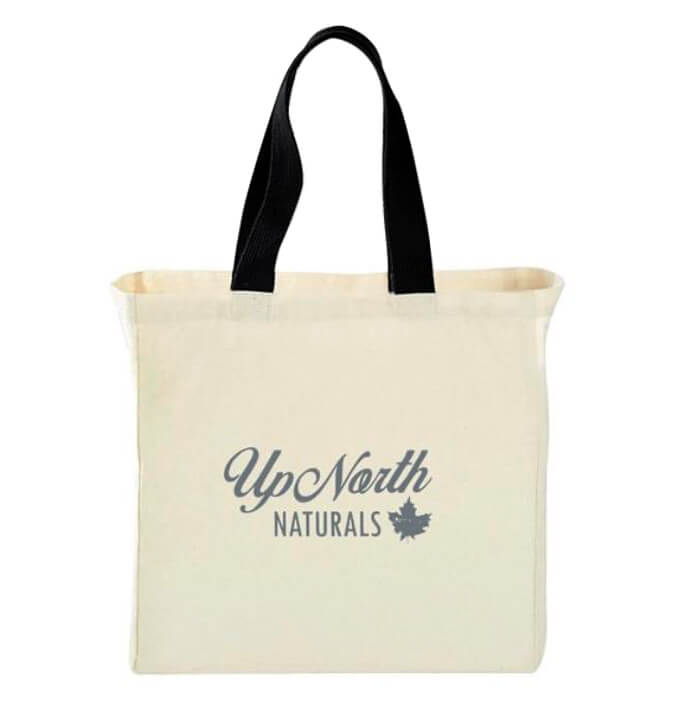 front image of beige tote with black handles and blue up north naturals logo on the front