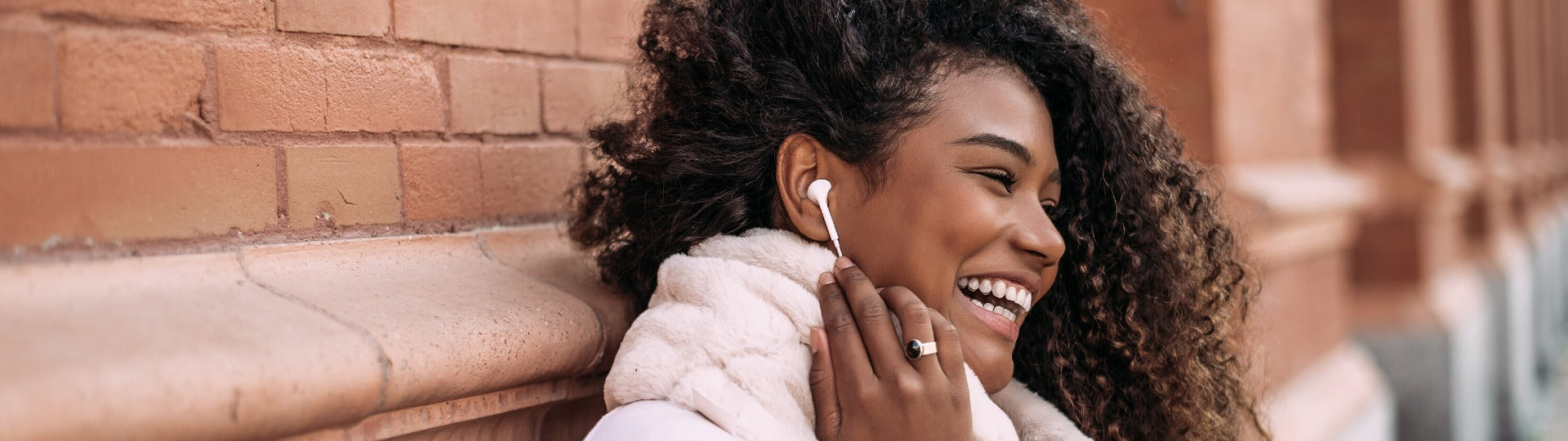 Woman with beautiful naturally curly hair outside listening to her earbud and laughing