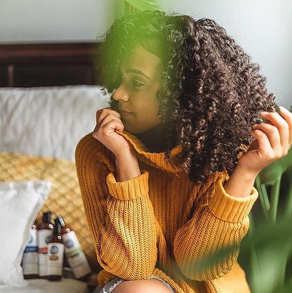 Lifestyle image of woman with beautiful naturally curly hair sitting on bed in comfy sweater with Up North Natural products in the background