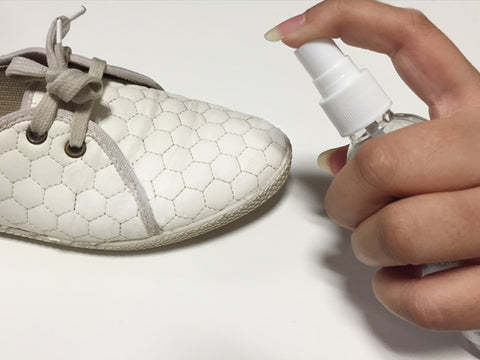 Spraying Vetro Power on a pair of shoes.