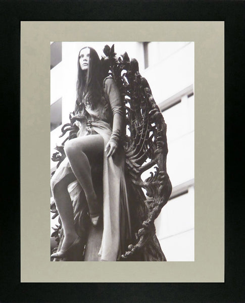 Brunette in long coat sitting on statue
