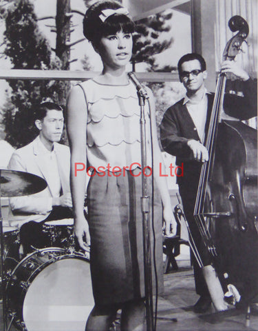Astrud Gilberto standing at a Microphone