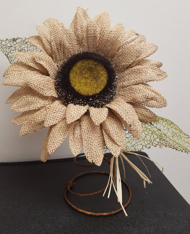 A burlap sunflower on top of a bedspring.