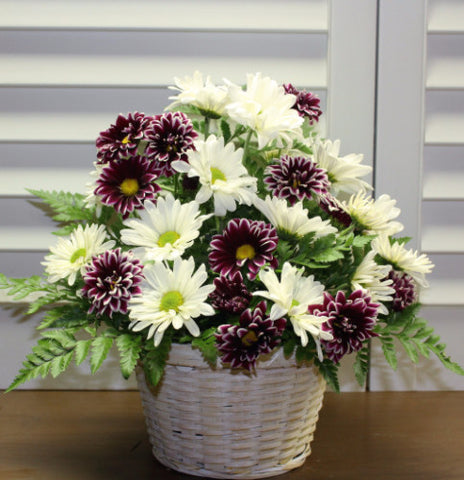 A white wicker basket with purple and white daisies arranged with greenery.