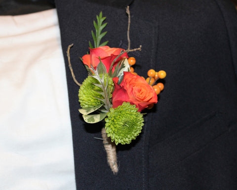 A boutonniere with 2 sweetheart roses and greenery.