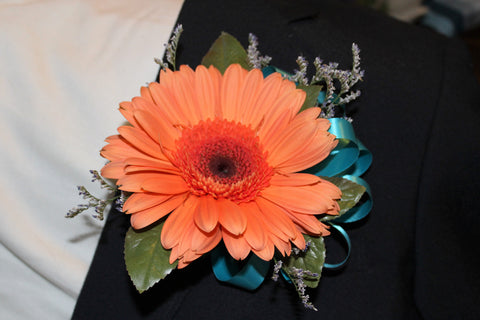 A boutonniere with gerbera daisy with greenery and a bow.